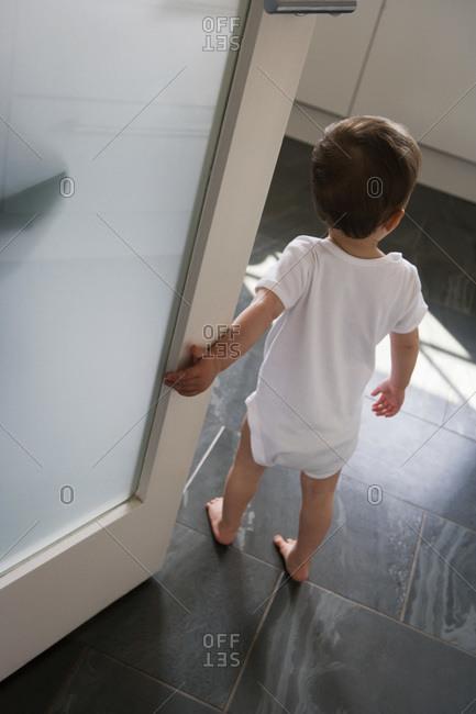 A little boy standing just inside a doorway