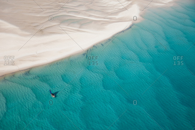 Traditional Mozambique boat sailing among sand drifts