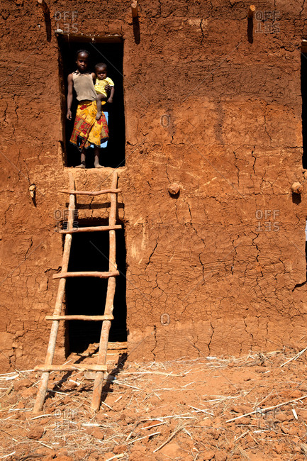 Young girl and baby in clay building Madagascar