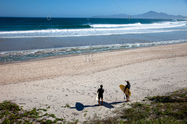 Two surfers watching waterscape at Madagascar