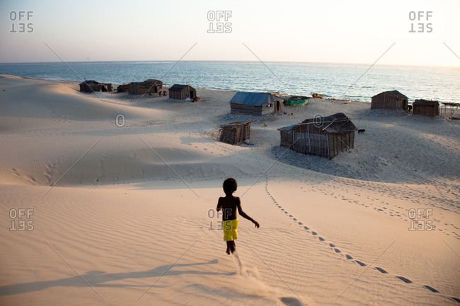 Young boy running in sand above village
