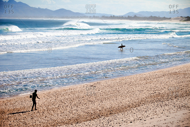 Surfer walks out to the surf break Local fisherman walks in foreground Madagascar