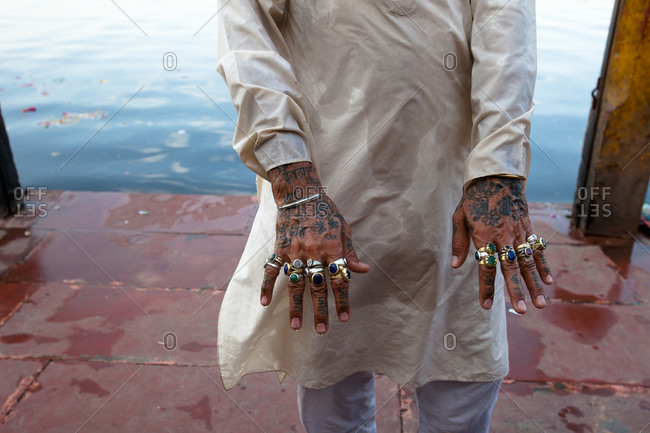 Mid-section view of Indian man shows his man rings on hands in Varanasi, India