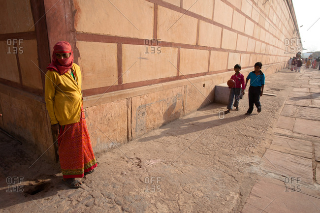 Indian woman stands against wall as children walk by in Jaipur, India