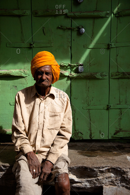 Indian man in his saffron color pagri, against green door in Pushkar, India