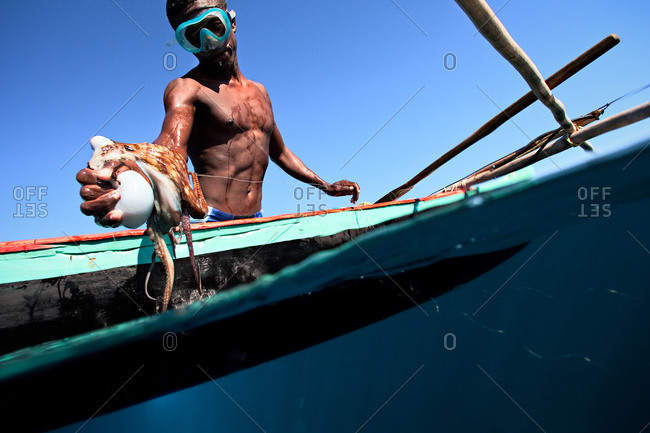 Young Vezo fisherman with octopus in Madagascar
