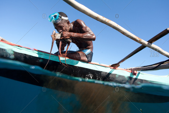 Vezo fisherman holding octopus in pirouge boat