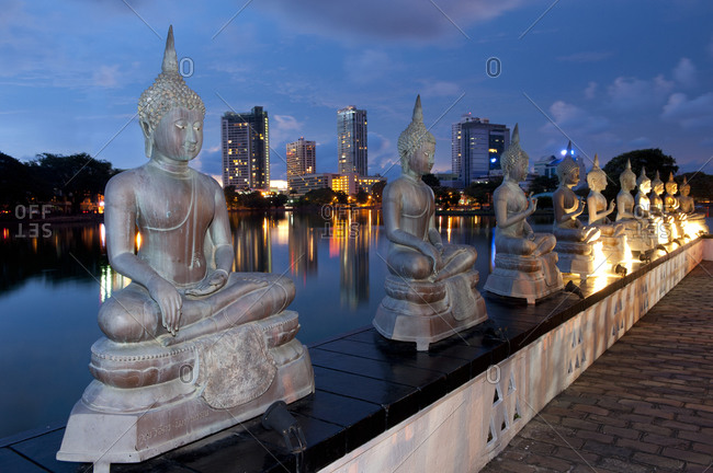 Buddha statues at twilight in front of the Colombo, Sri Lanka skyline.
