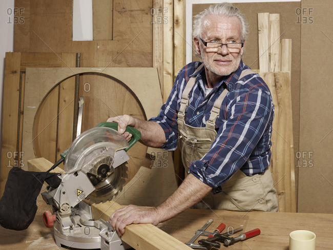 A man sawing wood in a workshop