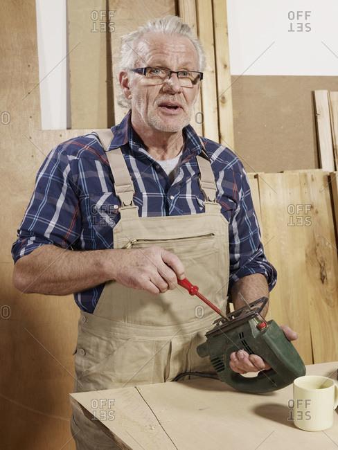 A man adjusting a power jigsaw