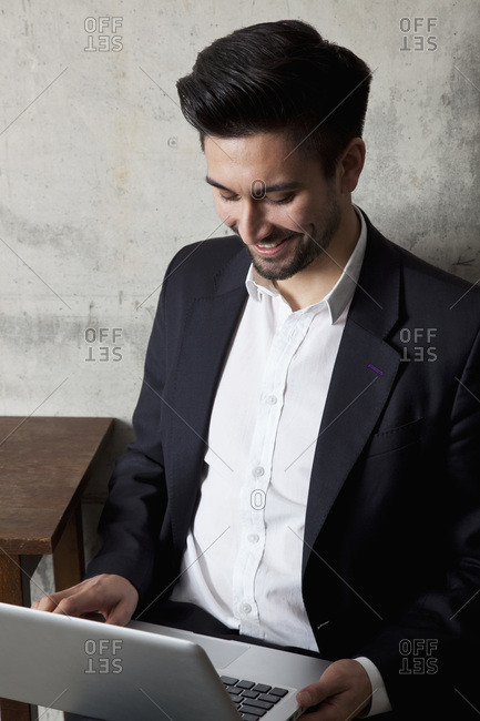 A smiling businessman working on a laptop, high angle view