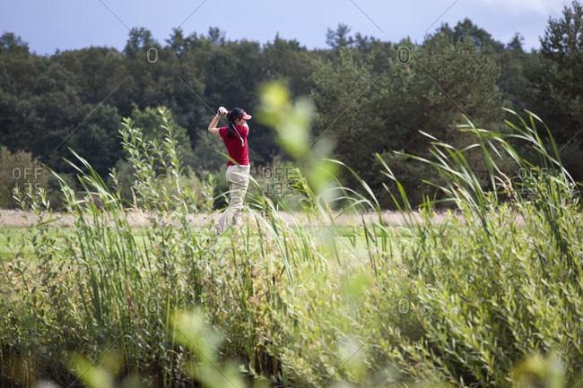 A female golfer teeing off, focus on background