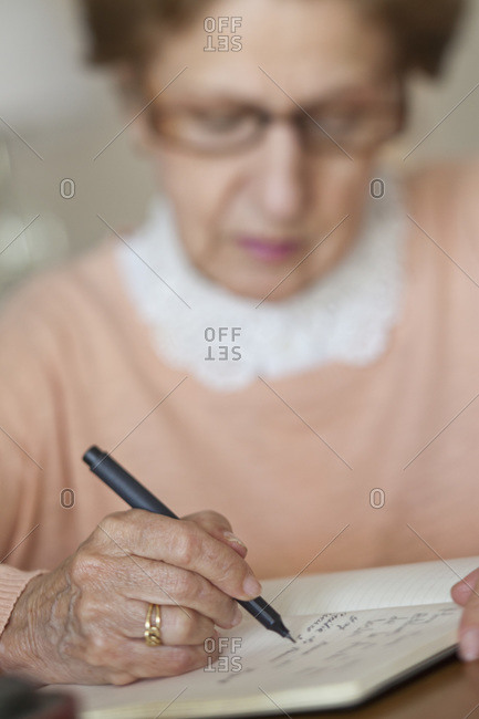 Detail of a senior woman writing in a note book
