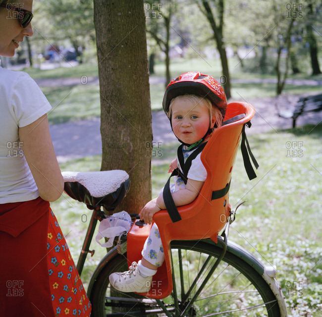 A little girl sitting in a child\'\'s seat on a bicycle