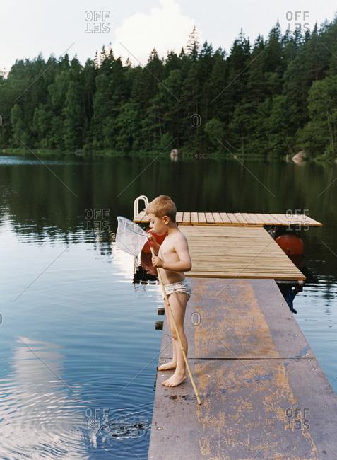 Boy in underwear standing on jetty looking inside fishing rod