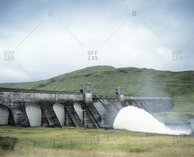 Hydroelectric dam. Water flowing out of the base of a dam at a hydroelectric power station, Perthshire, Scotland, UK.