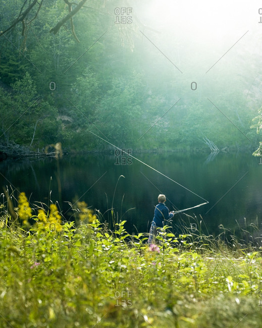 A boy fishing by a calm lake