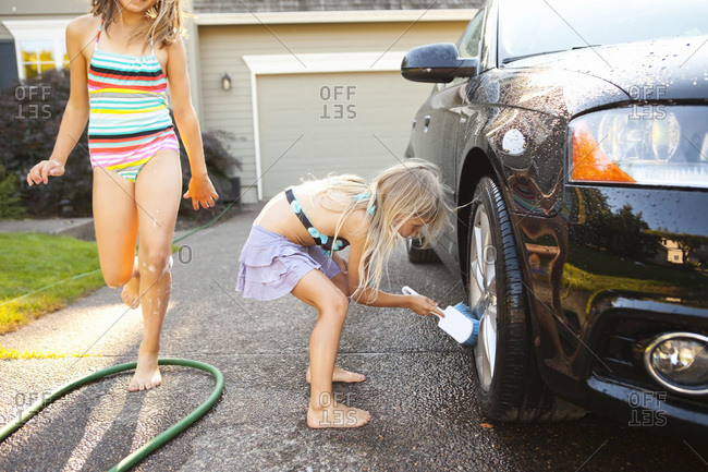 Sisters washing car in the driveway of their home on a sunny summer afternoon in Portland, Oregon, USA