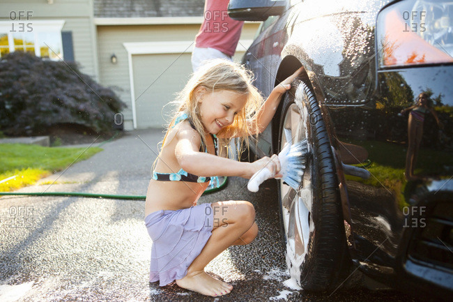 Young daughter helps father wash their car in the driveway of their home on a sunny summer afternoon in Portland, Oregon, USA