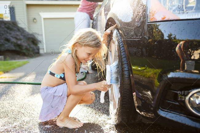 Young daughters help father wash their car in the driveway of their home on a sunny summer afternoon in Portland, Oregon, USA
