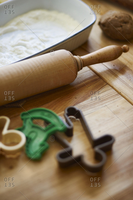 Rolling pin with cookie cutters on a cutting board with white flour to make Christmas cookies, Canada