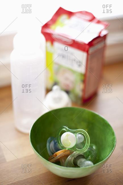 Baby nipples in bowl on hardwood floor