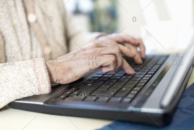 Midsection of senior woman using laptop at home
