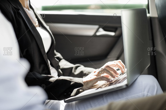 Midsection of businesswoman using laptop in taxi