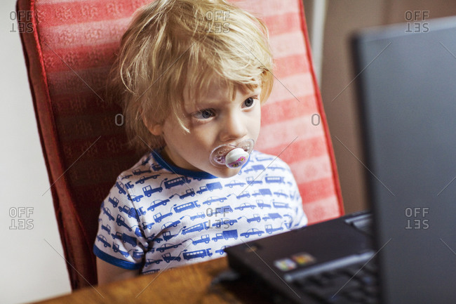 Small boy watching a film on a laptop,