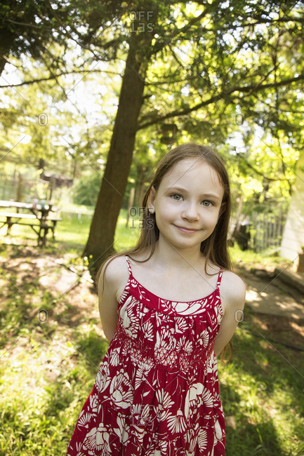 A young girl in a red floral summer dress in the shade of trees