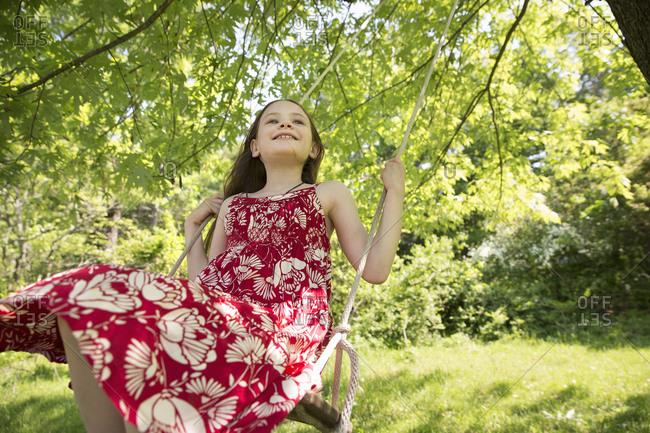 A girl in a sundress on a swing