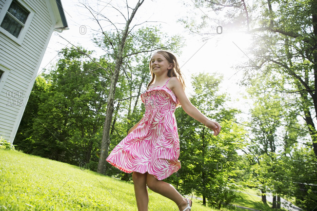 A young girl in a pink patterned sundress running across the grass under the trees