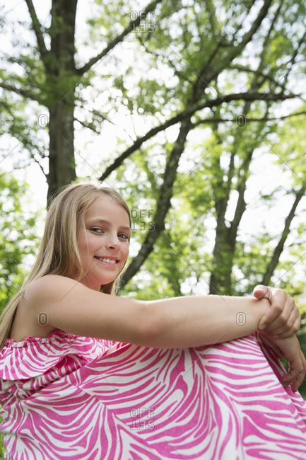 A young girl in a pink patterned sundress sitting on the grass under the trees