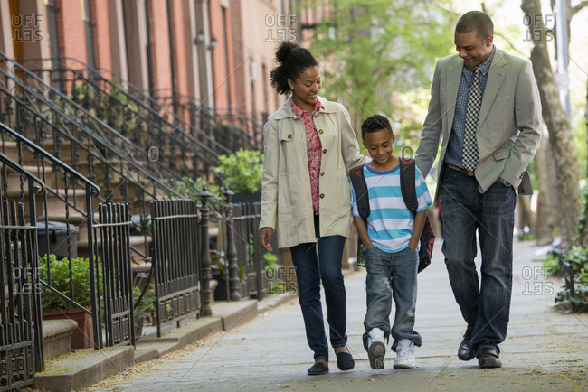 Two parents and a young boy walking together