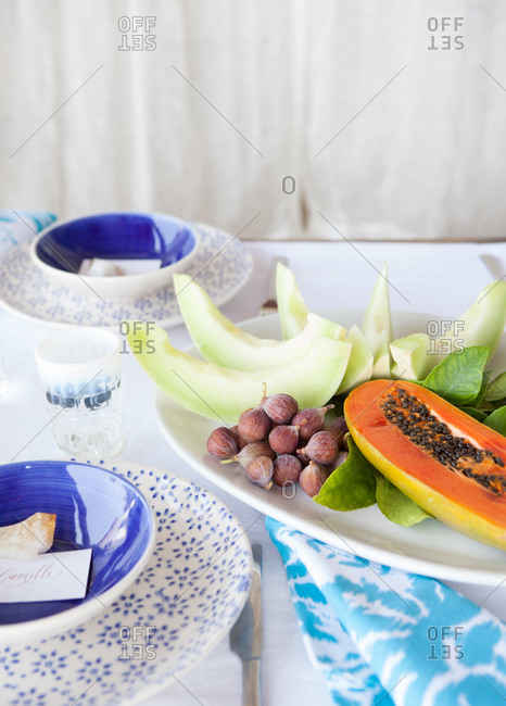 Still-life of fresh fruit platter from figs, honeydew melon wedges and papayas