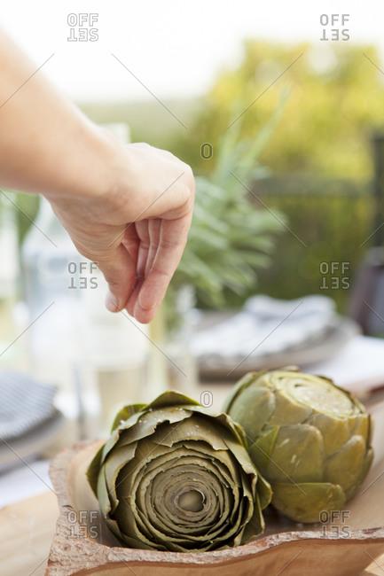 Female hand sprinkling salt over fresh artichoke globes