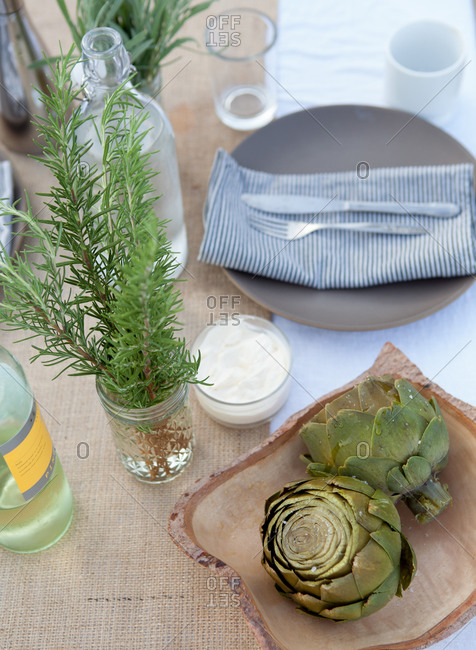 Still-life of fresh artichoke globes, bunch of rosemary and bottle of wine on table