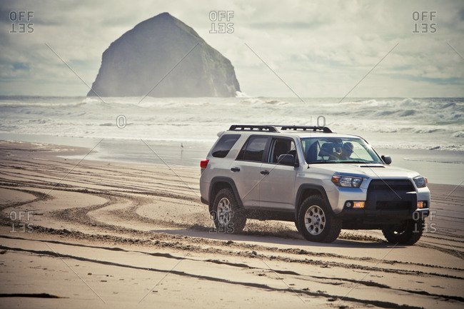 Pacific City, OR, USA - April 14, 2013: A man driving a 4x4 land cruiser on the beach