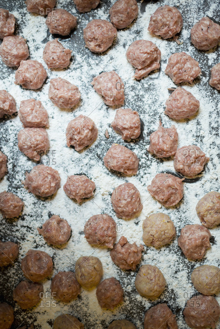 Raw meatballs with flour on iron plate