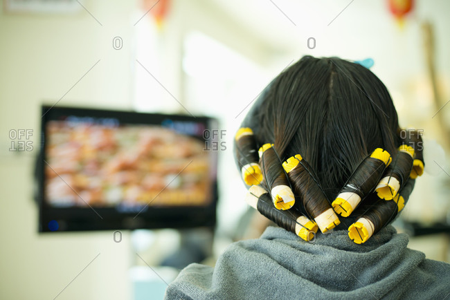 Young woman curling her hair in front of a TV screen