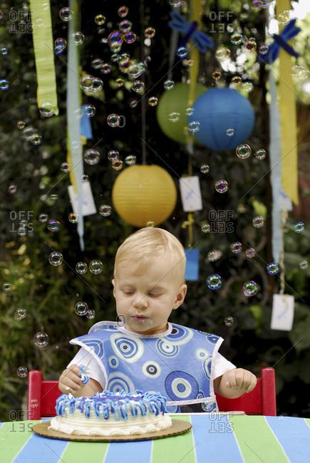 Little boy enjoying his first birthday cake