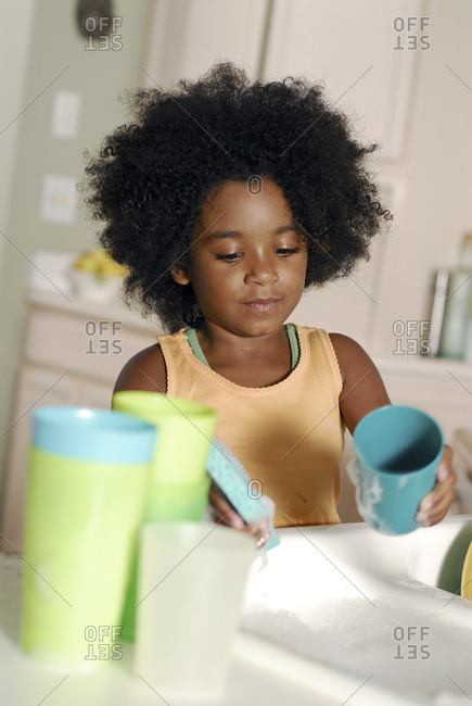 Young girl washing dishes at home