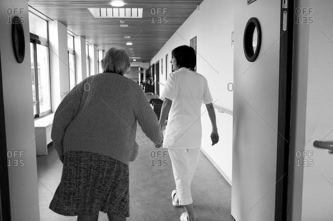 Nurse guides elderly woman