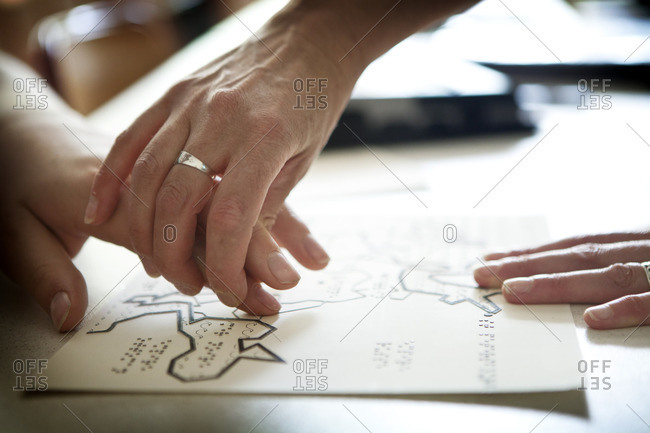 Close up of visually impaired person leaning to revise maps by touch
