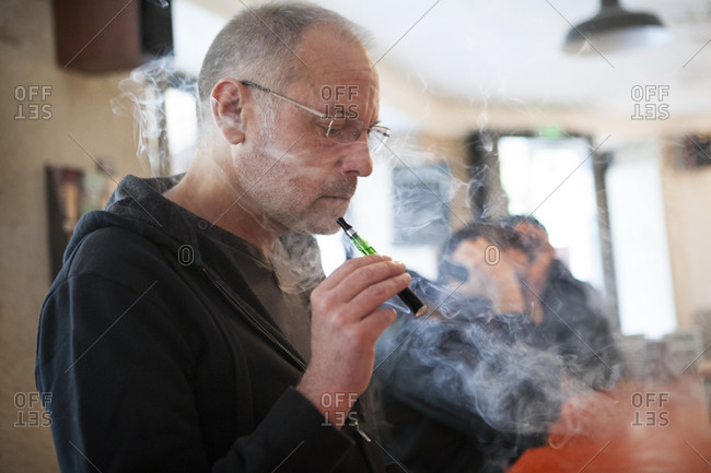 Man with an electronic cigarette in a public place