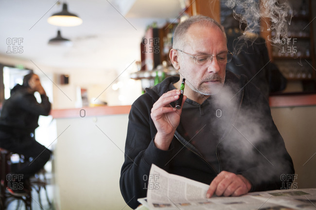Man smoking an electronic cigarette while reading the newspaper at a cafe
