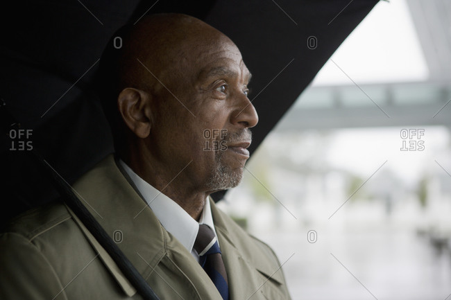 African businessman holding umbrella