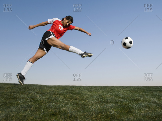 Mixed race woman kicking soccer ball