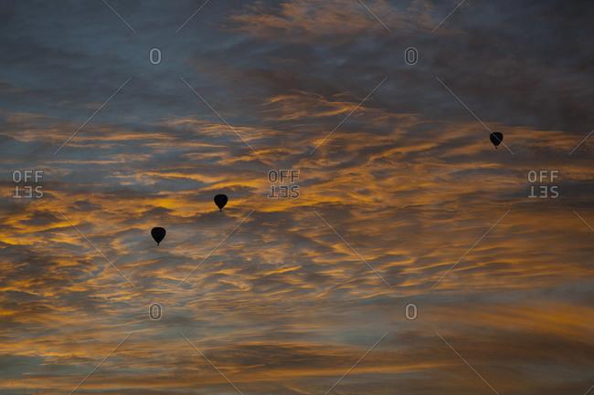 Three silhouetted hot air balloons against a dusk sky
