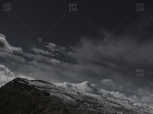 A dramatic cloudy sky above snow covered mountain